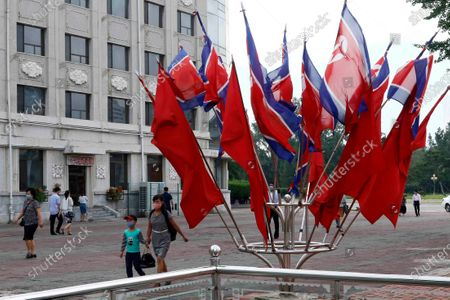 North Korean national flags are displayed on a street, in Pyongyang. North Koreans mark Foundation Day with floral offerings at the foot of giant statues of late leaders Kim Il Sung and Kim Jong Il