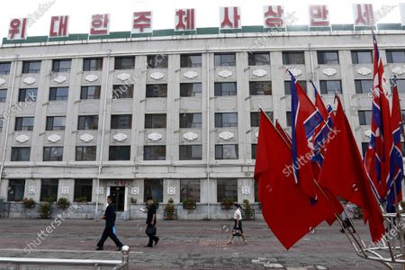 """People walk past a display of the national flags, in Pyongyang. North Koreans mark Foundation Day with floral offerings at the foot of giant statues of late leaders Kim Il Sung and Kim Jong Il. The slogan at top of a building reads """"Long live the great Juche Idea"""