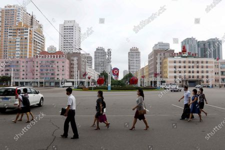 Stock Photo of People walk around the Pyongyang Railway Station in Pyongyang, in Pyongyang. North Koreans mark Foundation Day with floral offerings at the foot of giant statues of late leaders Kim Il Sung and Kim Jong Il