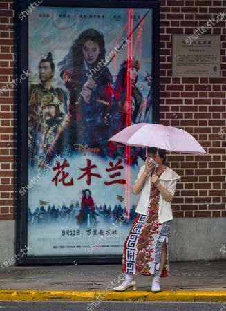 A woman stands in front of the movie theatre advertising Mulan movie in Shanghai, China, 09 September 2020. Disney's newest 200 million USD movie Mulan draws media attention after it was boycotted firstly in Hong Kong because of leading actress Liu Yifei support of China's policy for Hong Kong and crackdown of protestors. Later it was discovered that shooting of some parts of the movie took place in China's Xinjiang province which was accused by western media and governments for various human rights violations. The movie is set to have premiere in Chinese theatres on 11 September 2020 but pirated copies can be already found online, Chinese viewers of those copies already posted poor reviews on social media.