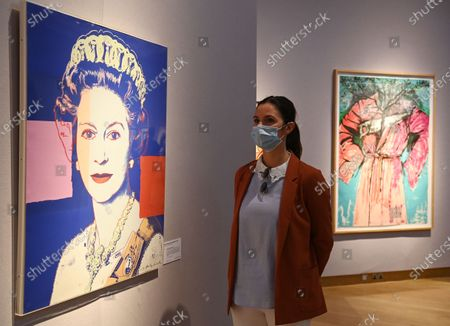A Christie's employee poses next to a painting entitled 'Queen Elizabeth II, from: Reigning Queens' (L) by US artist Andy Warhol in London, Britain, 09 September 2020. The Autumn Sale includes highlights of major artists Paul Cezanne, Andy Warhol, Banksy Prints and Picasso ceramics.