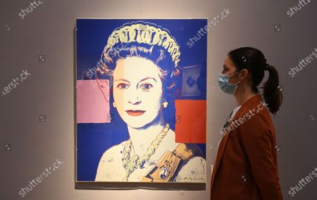 A Christie's employee poses next to a painting entitled 'Queen Elizabeth II, from: Reigning Queens' by US artist Andy Warhol in London, Britain, 09 September 2020. The Autumn Sale includes highlights of major artists Paul Cezanne, Andy Warhol, Banksy Prints and Picasso ceramics.