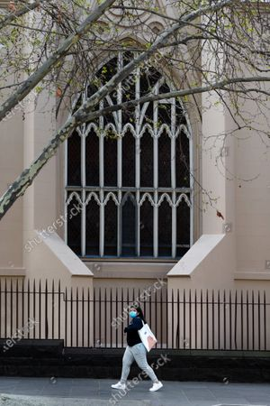 A woman walks under a large window at Saint Francis' Church on Elizabeth Street during COVID-19 in Melbourne, Australia. Victoria records a further 76 cases of Coronavirus over the past 24 hours, an increase from yesterday along with 11 deaths. This comes amid news that AstraZeneca pauses vaccine study.