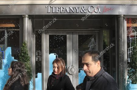 People walk past a Tiffany jeweler shop on the Champs Elysees avenue in Paris. LVMH is ending its monthslong pursuit of luxury jewelry retailer Tiffany & Co., citing in part the impact of proposed tariffs on French goods. The Paris-based conglomerate said that it needs more time to assess the impact of U.S. tariffs on French goods and cannot close the deal before year-end