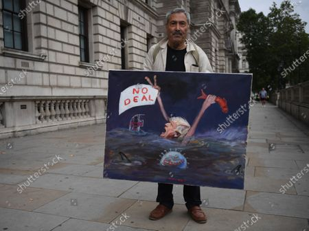 British satirical artist Kaya Mar poses with a painting in Westminster for the next round of Brexit talks in London, Britain, 09 September 2020. British and EU negotiators are holding talks this week to try thrash out a Brexit deal before a looming October deadline.