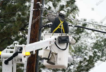 Cable company lineman toils to make a repair after a late summer storm packing high winds and snow swept through the intermountain West, in Denver. Forecasters predict that remnants of the storm will continue to bring snow and cold temperatures to the region through Wednesday before moving out onto the plains