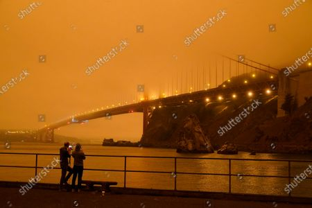 Stock Picture of Patrick Kenefick, left, and Dana Williams, both of Mill Valley, Calif., record the darkened Golden Gate Bridge covered with smoke from wildfires, from a pier at Fort Baker near Sausalito, Calif. The photo was taken at 9:47 a.m. in the morning