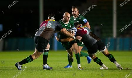 Jacob Atkins of London Irish is tackled by  Will Collier of Harlequins & Scott Baldwin of Harlequins