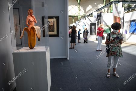 Stock Image of A woman walks pass an artwork entitled 'Chiquita banana 2007' by American artist Mel Ramos inside 'Galerie Patrice Trigano' during the Art Paris 2020 art fair held at the Grand Palais, in Paris, France, 09 September 2020. Art Paris is a modern and contemporary art fair, running from 10 to 13 September 2020. This year, some 112 galleries from 15 different countries are brought together.