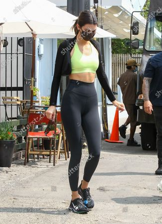 Kendall Jenner is seen wearing a lime green top and black Nike leggings
