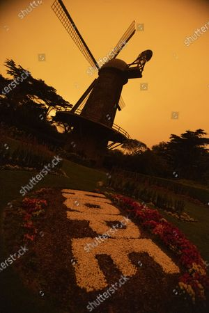 Dutch Windmill in the Queen Wilhelmina Tulip Garden Golden Gate Park under an orange haze caused by smoke from multiple wildfires in Oregon and California