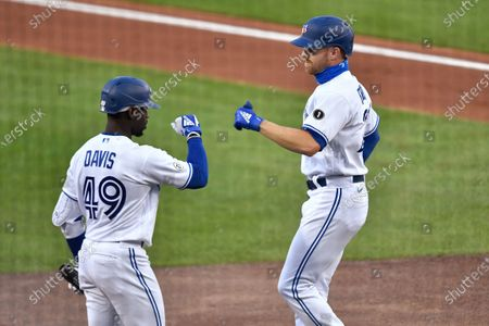 Toronto Blue Jays' Derek Fisher, right, is congratulated by Jonathan Davis after his two-run home run against the New York Yankees during the second inning of a baseball game in Buffalo, N.Y