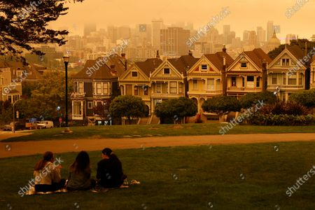 People sit at Alamo Square under an orange and yellow overcast sky overlooking the The Painted Ladies, the iconic row of historical Victorian homes with a downtown backdrop, in the afternoon in San Francisco, California, USA, 09 September 2020. California wildfire smoke high in the atmosphere over the San Francisco Bay Area blocked the sunlight and turned the sky a dark orange and yellow shade for most of the day.