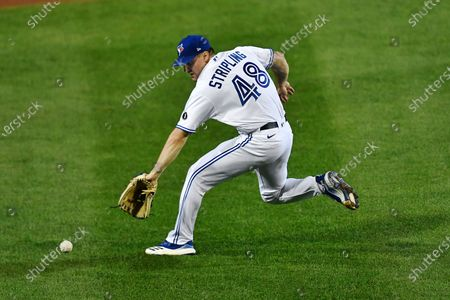Toronto Blue Jays pitcher Ross Stripling fields a grounder by New York Yankees' Clint Frazier during the seventh inning of a baseball game in Buffalo, N.Y., . Frazier was safe at first