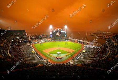 Stock Photo of Smoke from California wildfires obscures the sky over Oracle Park as the Seattle Mariners take batting practice before their baseball game against the San Francisco Giants, in San Francisco. People from San Francisco to Seattle woke Wednesday to hazy clouds of smoke lingering in the air, darkening the sky to an eerie orange glow that kept street lights illuminated into midday, all thanks to dozens of wildfires throughout the West