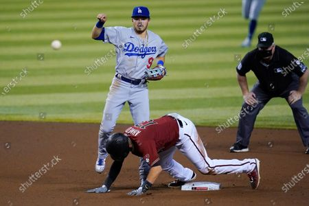 Los Angeles Dodgers second baseman Gavin Lux (9) watches his throw to first base to complete a double play against Arizona Diamondbacks' Christian Walker, after forcing out Nick Ahmed, while umpire Bill Miller, right, watches during the seventh inning of a baseball game, in Phoenix