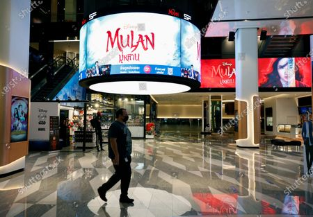 A foreigner walks next to an advertisement of Mulan movie at a cinema in Bangkok, Thailand, 10 September 2020. Thai pro-democracy activists join the global calling to boycott Disney's Mulan movie after it was found out that the leading actress Liu Yifei shared a post on social media supporting China's crackdown policy against Hong Kong protesters. According to the SEMrush data-trends company, the Google searches for 'Boycott Mulan' increased 1,900 per cent from the movie release date on 04 September 2020.