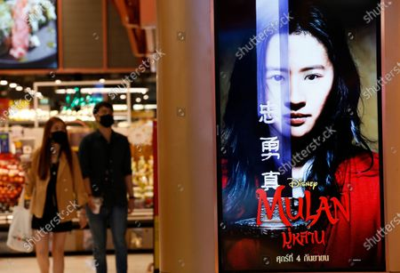 Thai people walk next to an advertisement of Mulan movie at a cinema in Bangkok, Thailand, 10 September 2020. Thai pro-democracy activists join the global calling to boycott Disney's Mulan movie after it was found out that the leading actress Liu Yifei shared a post on social media supporting China's crackdown policy against Hong Kong protesters. According to the SEMrush data-trends company, the Google searches for 'Boycott Mulan' increased 1,900 per cent from the movie release date on 04 September 2020.