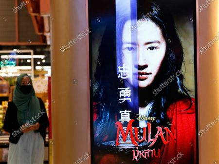 A Muslim woman walks next to an advertisement of Mulan movie at a cinema in Bangkok, Thailand, 10 September 2020. Thai pro-democracy activists join the global calling to boycott Disney's Mulan movie after it was found out that the leading actress Liu Yifei shared a post on social media supporting China's crackdown policy against Hong Kong protesters. According to the SEMrush data-trends company, the Google searches for 'Boycott Mulan' increased 1,900 per cent from the movie release date on 04 September 2020.