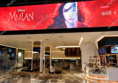 A Thai moviegoer sits next to an advertisement of Mulan movies at a cinema in Bangkok, Thailand, 10 September 2020. Thai pro-democracy activists join the global calling to boycott Disney's Mulan movie after it was found out that the leading actress Liu Yifei shared a post on social media supporting China's crackdown policy against Hong Kong protesters. According to the SEMrush data-trends company, the Google searches for 'Boycott Mulan' increased 1,900 per cent from the movie release date on 04 September 2020.