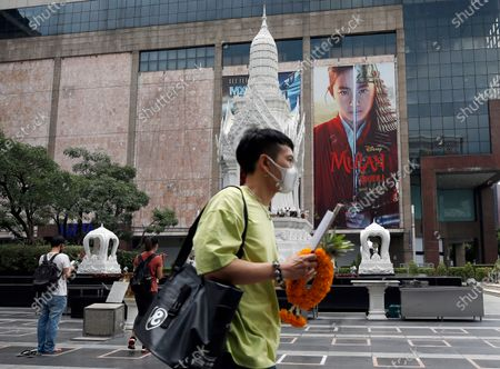 A Thai devotee arrives to pray at a shrine next to an advertising poster of Mulan movie at a shopping mall in Bangkok, Thailand, 10 September 2020. Thai pro-democracy activists join the global calling to boycott Disney's Mulan movie after it was found out that the leading actress Liu Yifei shared a post on social media supporting China's crackdown policy against Hong Kong protesters. According to the SEMrush data-trends company, the Google searches for 'Boycott Mulan' increased 1,900 per cent from the movie release date on 04 September 2020.