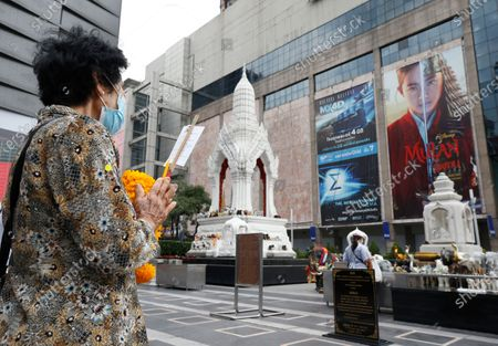 A Thai devotee offers prayers to a shrine next to an advertising poster of Mulan movie at a shopping mall in Bangkok, Thailand, 10 September 2020. Thai pro-democracy activists join the global calling to boycott Disney's Mulan movie after it was found out that the leading actress Liu Yifei shared a post on social media supporting China's crackdown policy against Hong Kong protesters. According to the SEMrush data-trends company, the Google searches for 'Boycott Mulan' increased 1,900 per cent from the movie release date on 04 September 2020.