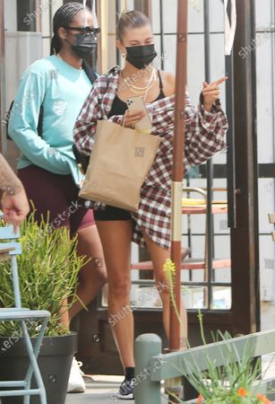 Hailey Bieber is seen wearing an oversized flannel shirt and Nike Pro bottoms