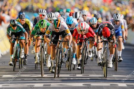 Ireland's Sam Bennett, center in white, crosses the finish line ahead of Australia's Caleb Ewan, right and third place, and second-placed Slovakia's Peter Sagan, third left in green, to win stage 10 of the Tour de France cycling race over 168.5 kilometers (104.7 miles) from Ile d'Oleron to Ile de Re, France
