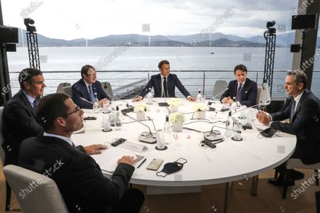 Clockwise from left, Malta's Prime Minister Robert Abela, Spain's Prime Minister Pedro Sanchez, Cyprus President Nikos Anastasiadis, France's President Emmanuel Macron, Italy's Prime Minister Giuseppe Conte and Greek Prime Minister Kyriakos Mitsotakis meet during an emergency summit in Porticcio, Corsica island, Thursday Sept.10, 2020. Leaders of EU countries on the Mediterranean Sea are holding an emergency summit in Corsica on Thursday amid fears of open conflict with Turkey stemming from mounting tensions over oil and gas drilling