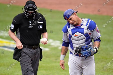 New York Mets catcher Wilson Ramos, right, reacts after taking a foul ball as home plate umpire Chris Conroy looks on during the second inning of a baseball game against the Baltimore Orioles, in Baltimore