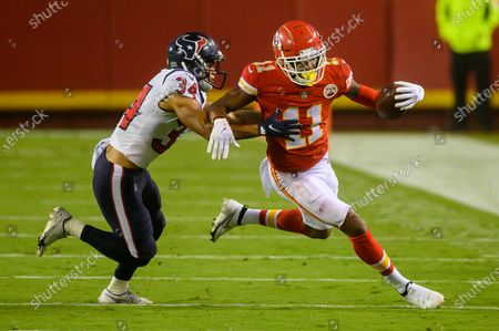 Houston Texans cornerback John Reid (34) tries to tackle Kansas City Chiefs wide receiver Demarcus Robinson (11) during an NFL football game, in Kansas City, Mo