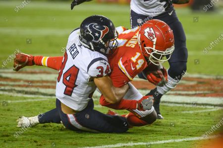 Kansas City Chiefs wide receiver Sammy Watkins (14) is tackled by Houston Texans cornerback John Reid (34) during an NFL football game, in Kansas City, Mo