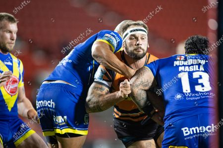George Griffin of Castleford is tackled by Ben Murdoch-Masila and Leilani Latu of Warrington.