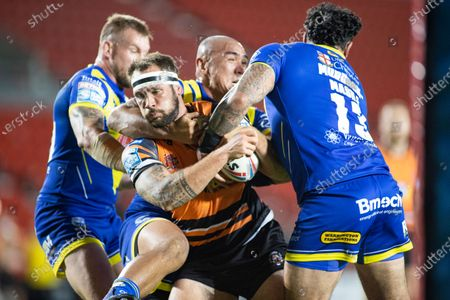 Stock Photo of George Griffin of Castleford is tackled by Ben Murdoch-Masila and Leilani Latu of Warrington.