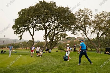 Jordan Spieth chips the ball onto the eighth green of the Silverado Resort North Course during the first round of the Safeway Open PGA golf tournament, in Napa, Calif. At left is Jim Furyk