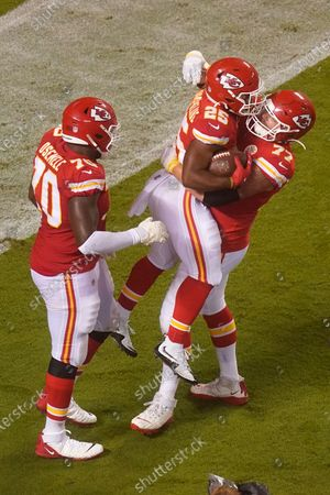 Kansas City Chiefs running back Clyde Edwards-Helaire (25) celebrates with Andrew Wylie (77) and Kelechi Osemele (70) after Edwards-Helaire scored a touchdown on a 27-yard run against the Houston Texans in the second half of an NFL football game, in Kansas City, Mo