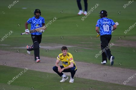 Stock Image of Calvin Harrison of Hampshire squatted down as Ravi Bopara and Luke Wright take a quick single