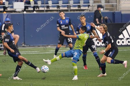 Seattle Sounders forward Raul Ruidiaz (9) kicks the ball between several San Jose Earthquakes during the first half of an MLS soccer match, in Seattle