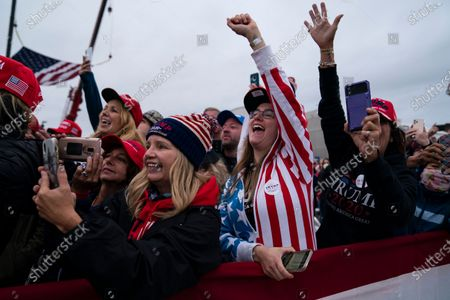 Supporters of President Donald Trump cheer as he arrives for a campaign rally at MBS International Airport, in Freeland, Mich
