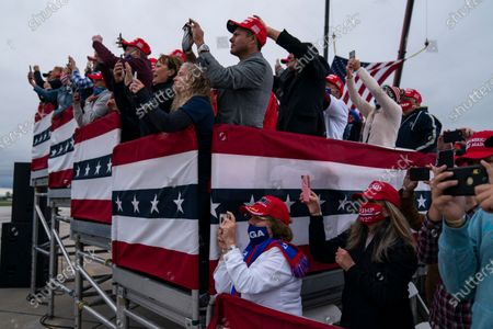 Supporters wait for the arrival of of President Donald Trump to a campaign rally at MBS International Airport, in Freeland, Mich