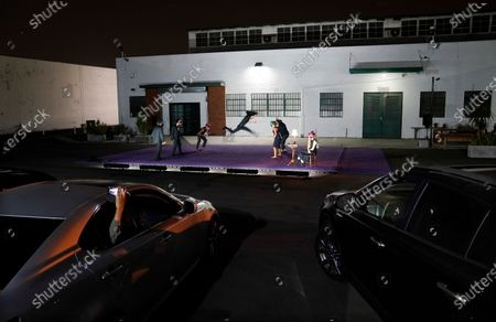 """Audience members in their cars watch """"Solo at Dusk,"""" a work by Bobbi Jene Smith in collaboration with Or Schraiber, during the opening night of L.A. Dance Project's Drive-In Dances series, in downtown Los Angeles. The series was conceived by L.A. Dance Project to safely bring live dance back to Los Angeles during the COVID-19 era by reimagining their 2020-2021 season as a drive-in experience"""