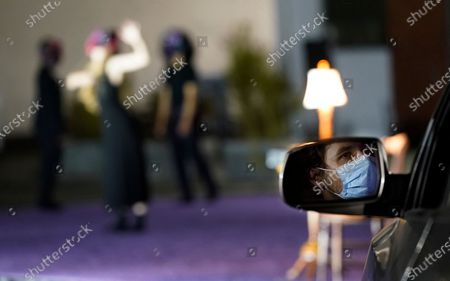 """An audience member is seen in his rear-view mirror as he watches a performance of """"Solo at Dusk,"""" a work by Bobbi Jene Smith in collaboration with Or Schraiber, during the opening night of L.A. Dance Project's Drive-In Dances series, in downtown Los Angeles. The series was conceived by L.A. Dance Project to safely bring live dance back to Los Angeles during the COVID-19 era by reimagining their 2020-2021 season as a drive-in experience"""