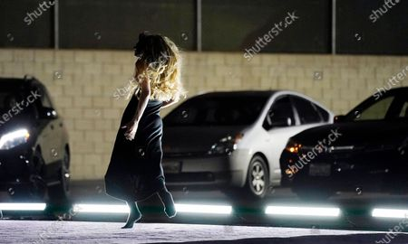 """Dancer Janie Taylor wears a mask as she performs during """"Solo at Dusk,"""" a work by Bobbi Jene Smith in collaboration with Or Schraiber, during the opening night of L.A. Dance Project's Drive-In Dances series, in downtown Los Angeles. The series was conceived by L.A. Dance Project to safely bring live dance back to Los Angeles during the COVID-19 era by reimagining their 2020-2021 season as a drive-in experience. Taylor also made all the masks for the production"""