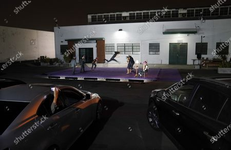 """Stock Image of Audience members in their cars watch """"Solo at Dusk,"""" a work by Bobbi Jene Smith in collaboration with Or Schraiber, during the opening night of L.A. Dance Project's Drive-In Dances series, in downtown Los Angeles. The series was conceived by L.A. Dance Project to safely bring live dance back to Los Angeles during the COVID-19 era by reimagining their 2020-2021 season as a drive-in experience"""