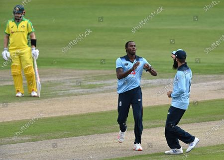 England's Jofra Archer, center, celebrates with teammate Moeen Ali, right, the dismissal of Australia's David Warner during the first ODI cricket match between England and Australia, at Old Trafford in Manchester, England