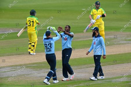 England's Jofra Archer, center, celebrates with teammates the dismissal of Australia's David Warner, left, during the first ODI cricket match between England and Australia, at Old Trafford in Manchester, England