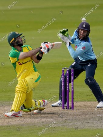 Australia's Glenn Maxwell, left, plays a shot past England's wicketkeeper Jos Buttler during the first ODI cricket match between England and Australia, at Old Trafford in Manchester, England