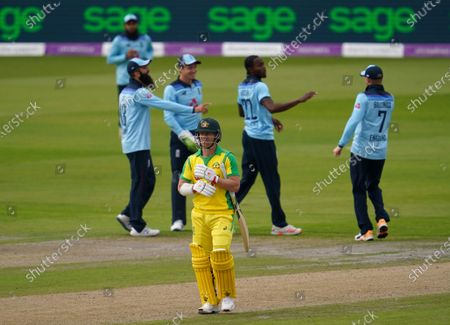 Australia's David Warner, front, walks off the field after being dismissed by England's Jofra Archer, second right, during the first ODI cricket match between England and Australia, at Old Trafford in Manchester, England