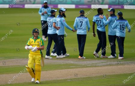 Australia's David Warner, left, walks off the field after being dismissed by England's Jofra Archer, third right, during the first ODI cricket match between England and Australia, at Old Trafford in Manchester, England