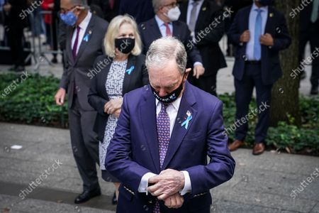 Former New York Mayor Mike Bloomberg checks his watch at the National September 11 Memorial and Museum, in New York. Americans will commemorate 9/11 with tributes that have been altered by coronavirus precautions and woven into the presidential campaign
